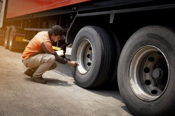 Truck driver inspecting safety daily check a truck wheels