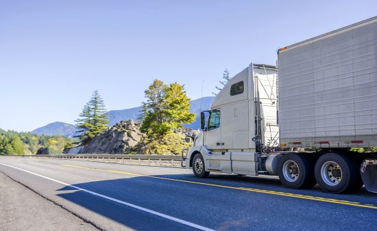 Big rig white bonnet long haul semi truck transporting frozen food in refrigerator semi trailer running on the road in Columbia Gorge